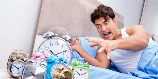 man with man alarm clocks he can't wake up